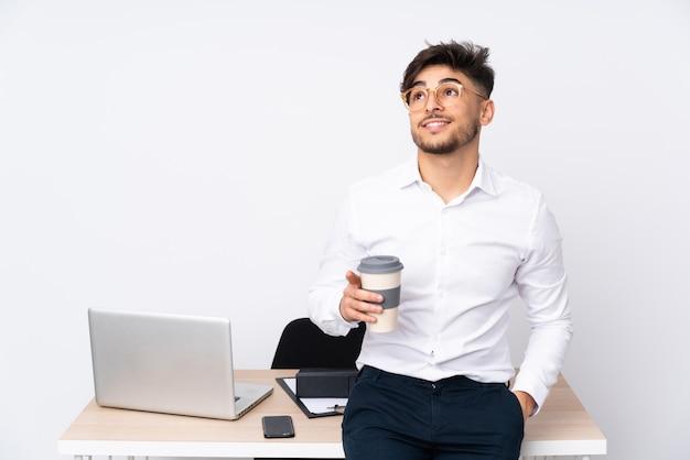 Arabischer mann in einem büro auf weißer wand, die eine idee beim aufschauen denkt