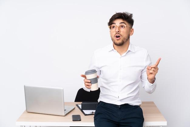 Arabischer mann in einem büro auf weißer wand, die eine idee denkt, die den finger nach oben zeigt