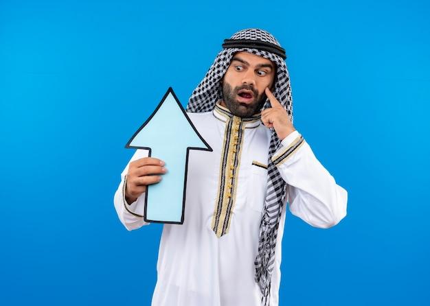 Arabischer mann in traditioneller kleidung, der großen blauen pfeil hält, der ihn überrascht und erstaunt betrachtet, der über blauer wand steht