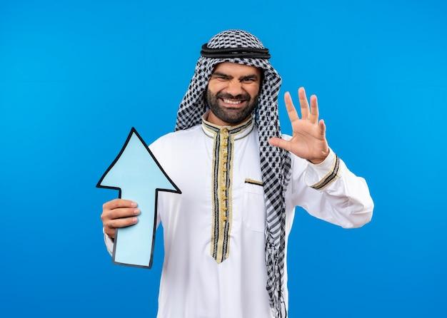 Arabischer mann in traditioneller kleidung, die großen blauen pfeil mit genervtem ausdruck auf gesicht steht, das über blauer wand steht
