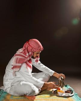 Arabischer mann mit auslaufendem tee der kandora
