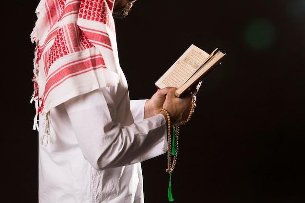Arabischer mann mit der kandora, die quran hält