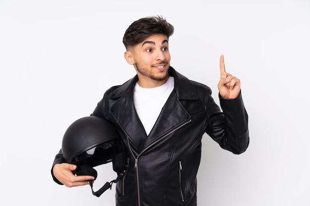 Arabischer mann mit einem motorradhelm auf weißer wand, die beabsichtigt, die lösung zu realisieren, während ein finger angehoben wird