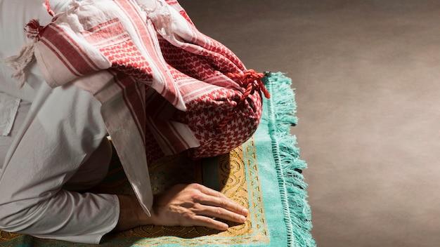 Arabischer mann mit kandorabogen auf gebetsteppich