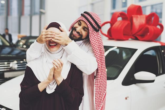Arabischer mann schließt augen für frauen-überraschungsgeschenk-auto.