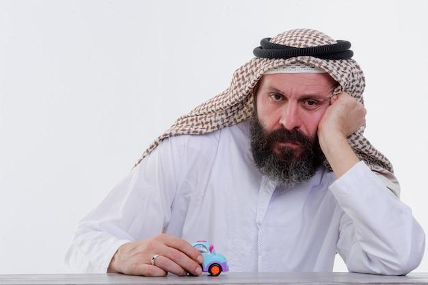 Arabischer mann spielt mit spielzeugauto