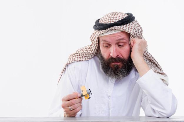 Arabischer mann spielt mit spielzeugflugzeug