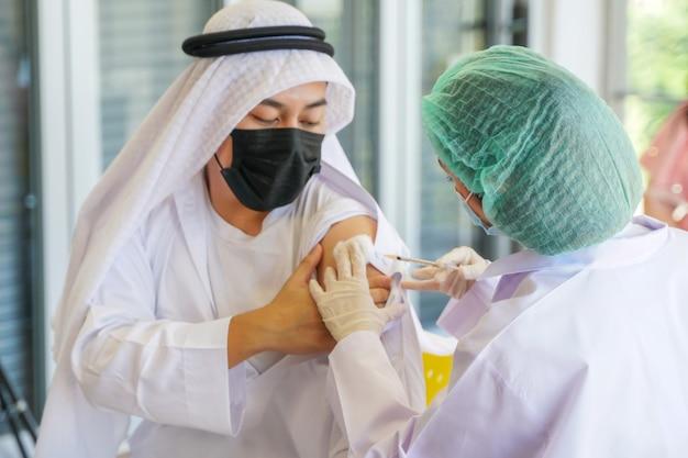 Arabischer muslimischer mann, der im krankenhaus sitzt, um einen covid-impfstoff zu bekommen, während eine handkrankenschwester den impfstoff injiziert