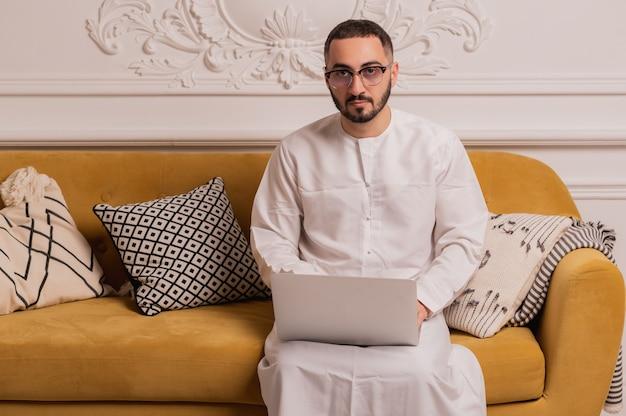 Arabischer programmierer, der zu hause am laptop arbeitet