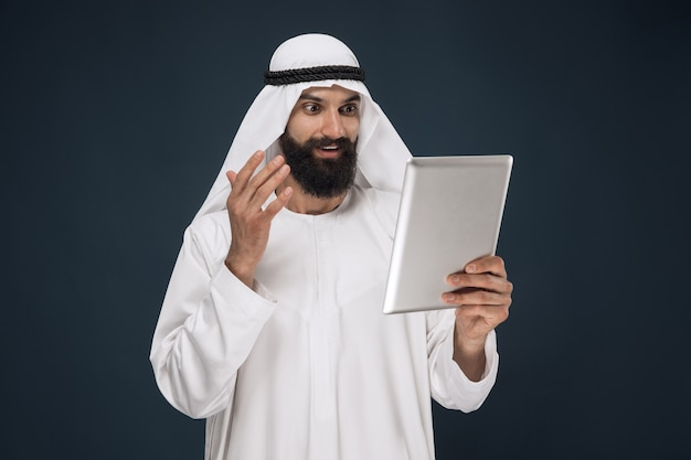 Arabischer saudischer geschäftsmann auf dunkelblauem studiohintergrund
