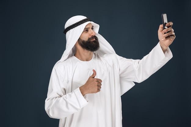 Arabischer saudischer mann auf dunkelblauem studiohintergrund