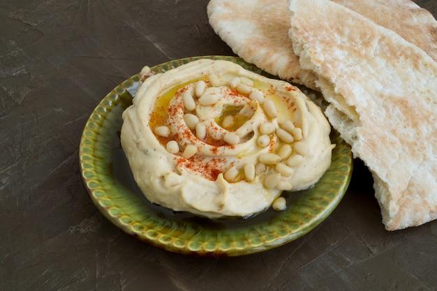 Arabischer snack von kichererbsen. hummus auf grauem hintergrund.