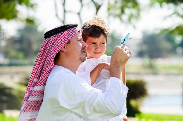 Arabischer sohn und vater drinnen posieren.