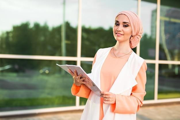 Arabischer student, der einen ordner hält