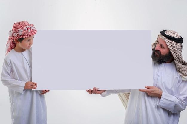Arabischer vater mit sohn hält weißes poster und streckt die zunge heraus stockfoto