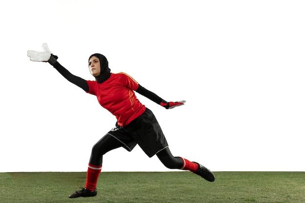 Arabischer weiblicher fußball- oder fußballspieler, torhüter auf weißem studiohintergrund. junge frau, die ball fängt, trainiert, ziele in bewegung und aktion schützt. konzept von sport, hobby, gesundem lebensstil.