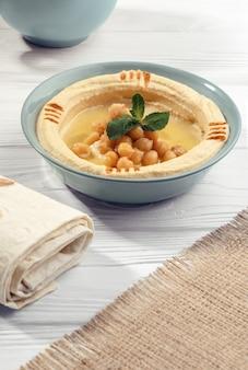 Arabisches hummus und brötchen und hessisches sacktextil auf holztisch