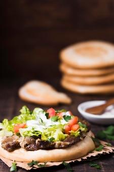 Arabisches kebab-sandwich im unscharfen hintergrund des fladenbrots