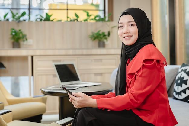 Arabisches muslimisches geschäftsfrau-mädchen lächelndes sitzendes porträt im geschäftsbüro, islam arbeitende frauenkonzept