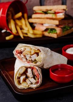 Arabisches shaurma in lavash mit pommes frites und club sandwiches dahinter.