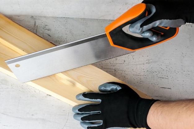 Arbeit am bau oder reparatur des hauses. unabhängiges update, renovierung. säge verwenden, handschuhe tragen.