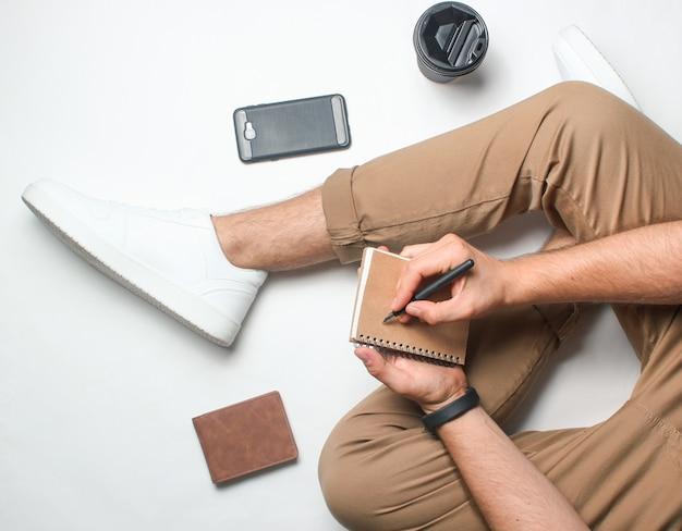 Arbeit eines journalisten. mann schreibt in ein notizbuch. fragment der männlichen beine in beigen hosen und weißen turnschuhen. draufsicht.