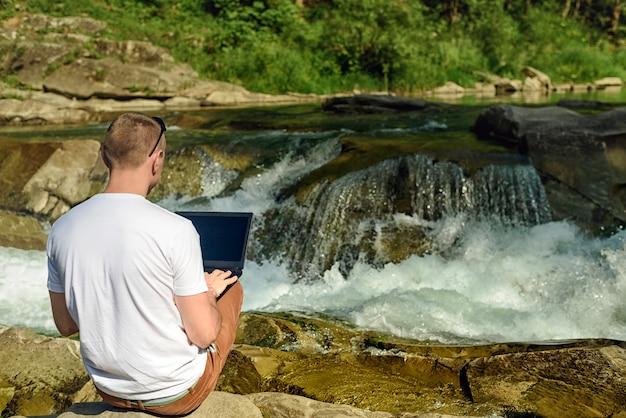 Arbeit im naturkonzept. mann mit dem notizbuch, das in der bank von fluss über dem wasserfall und den grünen bäumen sitzt. rückansicht