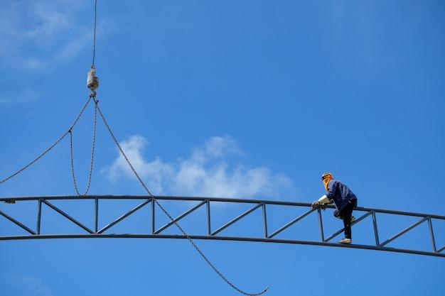Arbeit in der höhe, bauarbeiter klettern hoch, um ohne sicherheitsausrüstung zu arbeiten.
