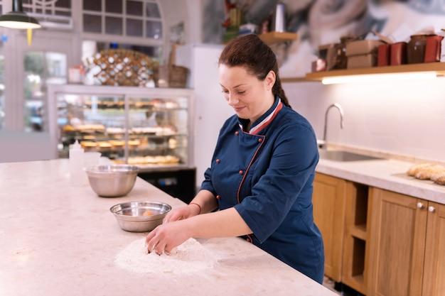Arbeit in der küche. strahlender dunkelhaariger bäcker, der sich freudig fühlt, wenn er in der küche arbeitet und croissants macht