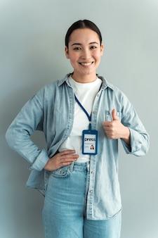 Arbeit ist getan! porträt einer jungen frau mit abzeichen, die jeanshemd trägt, stehend und daumen hoch zeigt und in die kamera schaut. grauer hintergrund, innenstudioaufnahme isoliert