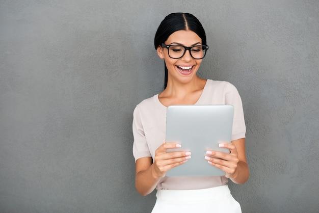 Arbeit ist gut gemacht! fröhliche junge geschäftsfrau, die digitale tablette hält und sie im stehen vor grauem hintergrund betrachtet