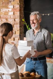 Arbeit, kommunikation. langhaarige frau, die mit dem rücken zur kamera steht und packboxen an freudigen erwachsenen mann in der bäckerei übergibt