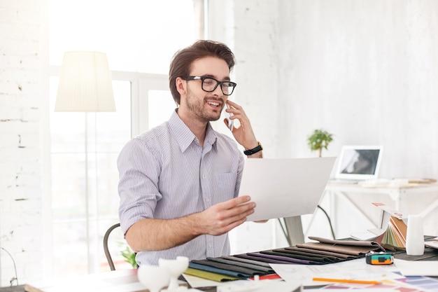 Arbeit machen. erfreuter perlenmann, der am telefon spricht und ein blatt papier hält