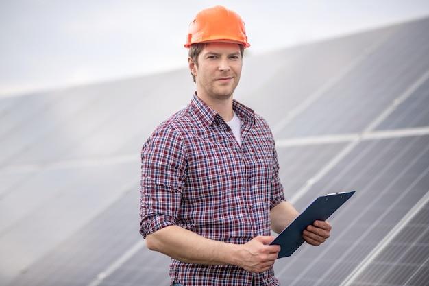 Arbeit, vertrauen. selbstbewusster junger erwachsener mann in hellem schutzhelm und kariertem hemd mit dokumentenmappe in der nähe von objekten im freien