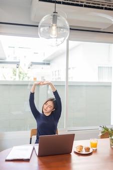 Arbeit von zu hause aus konzept einer unternehmerin, die entspannt ihre arme streckt, während sie aus der ferne in ihrem haus arbeitet.