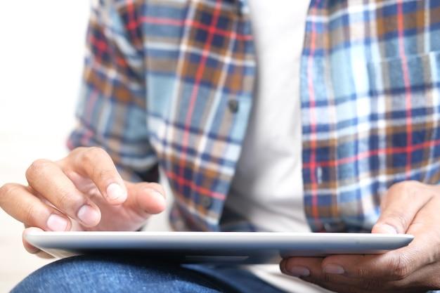 Arbeit von zu hause konzept junger mann, der auf digitalem tablett sitzt auf boden