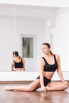 Arbeite an deinem körper. professionelle begabte junge frau, die auf dem boden sitzt und ihre beine während des trainings beugt