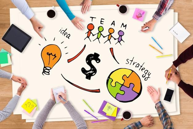 Arbeiten als ein team. draufsicht nahaufnahme von menschen, die am holztisch mit bunten skizzen darauf sitzen on