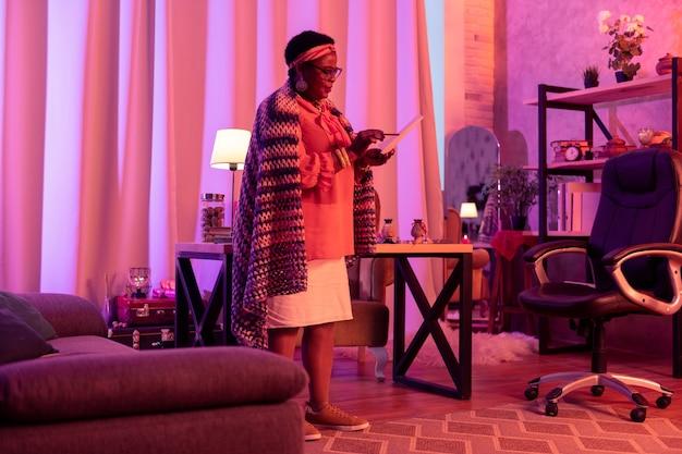 Arbeiten am horoskop. afroamerikaner pralle wahrsagerin, die brillen trägt, die ein horoskop vorbereiten