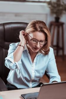 Arbeiten am laptop. blonde reife frau in bürokleidung und brille, die am laptop arbeitet