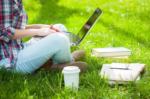 Arbeiten am laptop im freien. abgeschnittenes bild einer studentin, die am laptop arbeitet, während sie in einem park mit büchern um sie herum sitzt