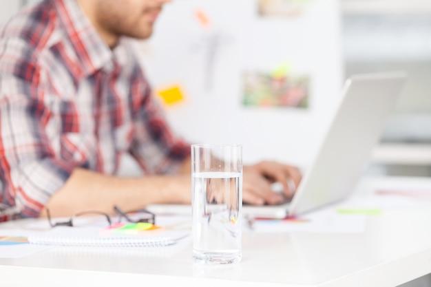 Arbeiten an einem kreativen projekt. abgeschnittenes bild eines jungen mannes, der am laptop arbeitet, während er an seinem arbeitsplatz sitzt