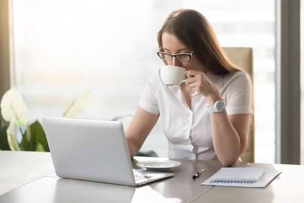 Arbeiten an trinkendem kaffee der computergeschäftsfrau
