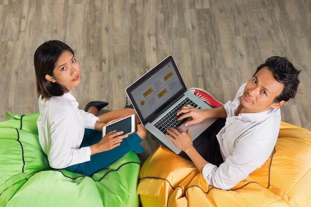 Arbeiten asiatischer mann und frau, die auf helle stühle