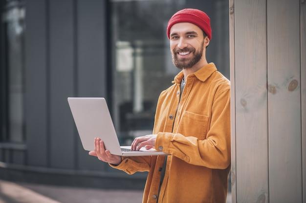 Arbeiten. bärtiger junger mann in einem roten hut, der an einem laptop arbeitet