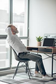 Arbeiten . ein reifer selbstständiger mann, der zu hause arbeitet und müde aussieht