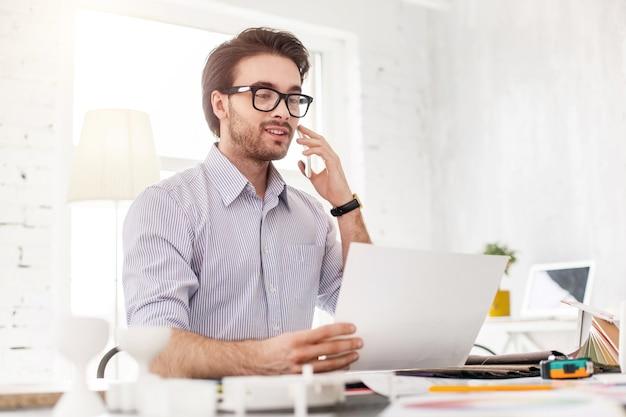 Arbeiten. frohes perlenbesetztes mann, das am telefon spricht und ein blatt papier hält