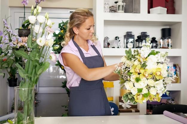 Arbeiten im blumenladen. professioneller florist kreiert einen riesigen schönen blumenstrauß aus frischen weißen rosen, gelben lilien und grünen blättern. verkäufer an ihrem arbeitsplatz in uniform mit blumenstrauß.