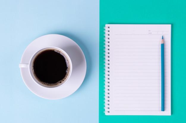 Arbeiten im bürokonzept. schwarzer kaffee und notizbuch mit bleistift auf tabellenhintergrund im büro.