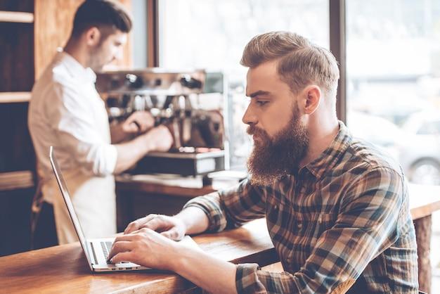 Arbeiten im café. seitenansicht eines jungen gutaussehenden bärtigen mannes, der seinen laptop benutzt, während er an der bartheke im café mit barista im hintergrund sitzt sitting